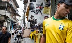 A resident stands in front of an advertisement for online combat games on the streets of Complexo do Alemao, Brazil