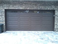 Amarr Lincoln Collection 3000 Long Panel in a dark brown finish with full sunray window inserts. This is an custom garage door with an R-Value of Custom Garage Doors, Custom Garages, Brown Wood, Dark Brown, Brown Garage Door, Window Inserts, Garage Door Makeover, Garage Door Installation