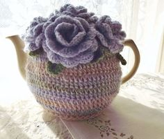 Garden party perfect! Pretty lilac roses adorn this soft, pastel striped crochet tea cozy. It is crocheted in a lovey, thick and stretchy stitch that will make this cozy adaptable to a wide selection of shapes and sizes of tea pot. This tea cozy will fit a 4 - 6 cup tea pot.