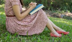 Young woman reading bible in natural park
