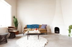 "The living room of Krysta and Joel's ""Ghost Ranch"" inspired adobe home, located in the historic Barrio Libre neighborhood in Tucson, is a one-of-a-kind space. It even comes complete with the original adobe fireplace."
