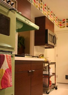 Cute remodel job keeping the vintage appliances. Nice Orla Keily wallpaper accent, too.