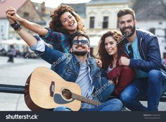 Group of young people hangout  on street in downtown.They standing by the city square,drinking and playing guitar.