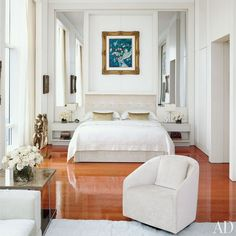 A Chagall painting is mounted above the master suite's bed, which is dressed in…