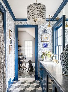 In the butler's pantry, Brunschwig & Fils' Les Touches pattern covers the walls, the pendant shade, the picture mats, and the doorway drape. This typically British form of repetition takes on new life when paired with cork flooring laid to three-dimensional effect. Danielle Rollins home tour