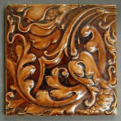 "Craven Dunnill and Co relief moulded dust pressed tile with an allover floral pattern, brown glaze, 6"" square, c1900"