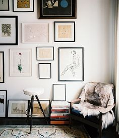 This stunning wall has art spanning the entire space, including a few pieces propped on the floor.