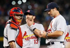 St. Louis Cardinals manager Mike Matheny, right, looks down at the baseball as he stands next to catcher Yadier Molina, left, and Matt Carpenter (13) after Matheny removed pitcher Sam Freeman during the eighth inning of a baseball game against the Arizona Diamondbacks Saturday, Sept. 27, 2014, in Phoenix. The Diamondbacks won 5-2. (AP Photo/Ross D. Franklin)
