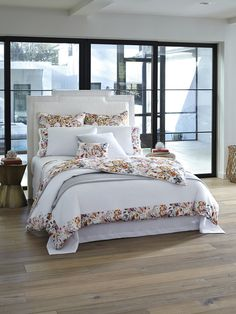 Este's sateen appliqué dresses a bed top with abundant, lush leaves, petals and tendrils of warm color.