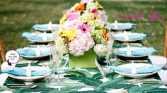 Bold turquoise napkins, banana leaf table cloth, elephant napkin rings, bamboo rimmed plates, and bamboo flatware