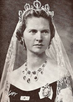 Princess Sibilla of Sweden wearing the Connaught Tiara - 5 upright loops of forget-me-not wreaths with a diamond pendant suspended in each. Between the loops, upside down bows support single diamond uprights. It can be worn as a necklace, or the diamond pendants can be worn on a chain or as earrings.