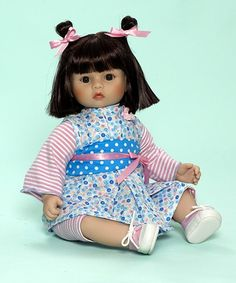 Bundle Of Love 14-inch Asian baby doll with brown eyes and whose center-parted brown hair with bangs is pulled up into two loops on top of her head and tied with pink ribbons. She wears a white cotton, with blue and pink floral print, kimono style dress over a one-piece romper with matching leggings. The pink, white and silver striped romper and leggings are finished by a light blue lettuce stitch. The kimono, which has an inverted box pleat, asymmetrical closures and a crocheted flower at…
