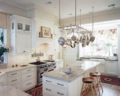 The light colors make this small kitchen look larger. And I dig the pot rack over the island.
