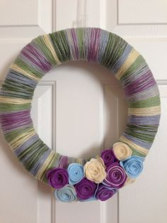 Spring yarn wreath! Blue, light green, dark green, yellow, light purple & dark purple yarn wrapped straw wreath with handmade felt rosettes. on Etsy, $20.00