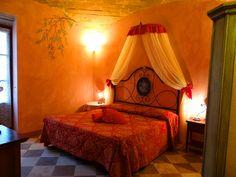 Camera Il Glicine dell'agriturismo romantico Taverna di Bibbiano. La camera è arredata con cura con mobili di alto artigianato toscano e dettagli preziosi, è al piano terra ed ha accesso diretto al giardino dell'agriturismo.