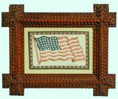 A Tramp Art cross-cornered frame with an American flag flannel. These colorful flags were given away as premiums upon purchase of various products including cigarettes and cigars between 1910–1915. They were used to make quilts, pillows cases and tabletop mats. The flag has USA on the bottom. Found in the Midwest, circa 1910–1920.