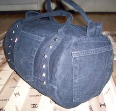 Black mini duffel with cone studs on the front and bottom made from Levi's denim jeans. Corded handles.