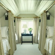 Beds under the attic eaves, each with their own privacy curtains. Great for when family comes visiting from out of town.