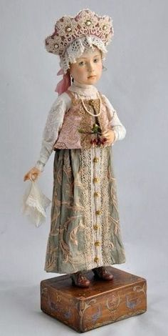 Doll in Russian costume holds some cherries in its hand.