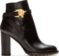 Ankle-high buffed leather boots in black. Round toe. Wraparound straps at ankle with gold-tone pin-buckle closure shaped like a unicorn's head. Tan leather sole. Tonal stitching.