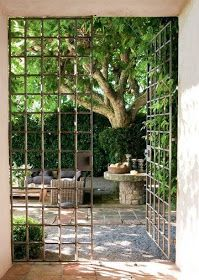 PROVENCE love the gates into another section of garden. Mirror on back wall adds more depth