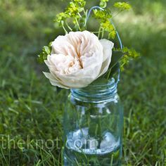 Single peony blooms in blue mason jars hung along the ceremony aisle.