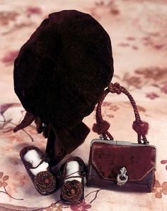 """Dolls Velvet Cap,Leather shoes and Leather Purse 3"""" inside head width. 3""""l. purse. 2""""l. shoes. Comprising black kidskin shoes with brown overcast stitching,loop and button closures,brown silk rosettes,marked """"C.M."""" (in oval); with brown leather purse with maroon velvet flap and braid handle,and silver clasp; and maroon velvet beret-style cap with velvet tassel trim. Circa 1885."""
