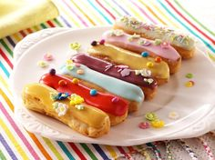 Mini Éclairs Recipe: These vibrant mini éclairs offer a decadent taste of crisp choux pastry oozing with delicious cream and topped with colourful fondant icing and sprinkles. - One of hundreds of delicious recipes from Dr. Oetker!
