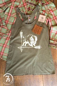 """- """"Savannah Sevens Cattle Co."""" steer head graphic tank - Black graphic on olive - Fitted thru the bust with a slightly flowy fit thru the bodice - Size XSmall fits 0-3 - Shown styled with The Durant c"""
