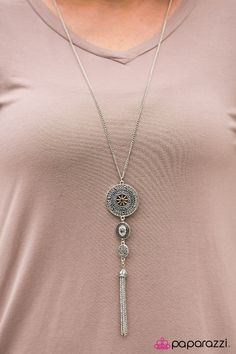 COURAGE IS MY COMPASS - BROWN ($5) Three ornate silver frames decrease in size as they trickle down the chest, creating a dramatic pendant. Infused with rhinestone centers, the compass-like pendants give way to a playful silver tassel for a whimsical finish. Features an adjustable clasp closure. Includes a pair of free matching earrings.