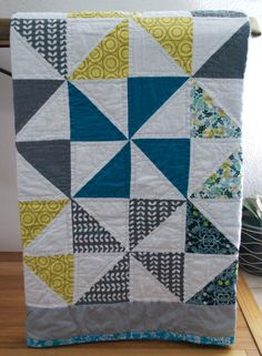 A beautiful, hand quilted, modern quilt made with 100% premium cotton fabrics and batting in Teal, Gray, Yellow and White in a pinwheel pattern.  $450