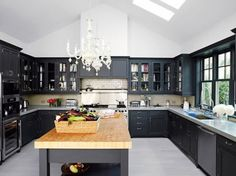 black kitchen with ~butcher block island ~light floor and ceiling ~chandelier ~subway tiled backsplash ~trim painted to match cabinets ~glass doors on uppers