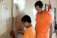 Volunteer Amable working with one of of his students on Alphabets.