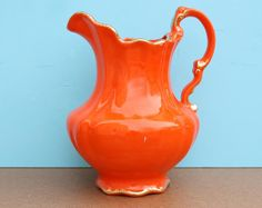 Orange Pottery Barn pitcher with gold trim (perfect for purple flowers).