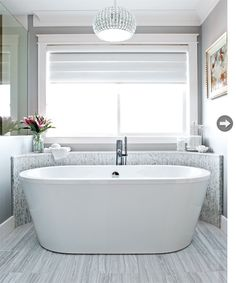 Surrey, BC house. Designer: Victoria McKenney of Enviable Designs. An elegant chandelier takes a room from basic to beautiful. A curved tiled wall sets off this modern soaker tub.