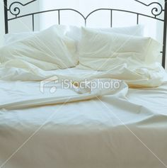 white bed in front of window.