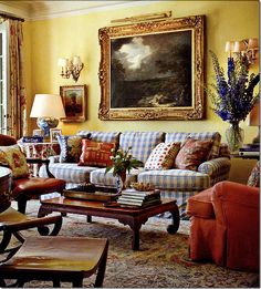 REALLY, REALLY LOVE THIS ROOM! Warm yellow walls, blue buffalo check sofa, huge & ornate gilt frame, red chair, blue & white ginger jar lamp, mismatched throw pillows...a formal living room with a family room feel.