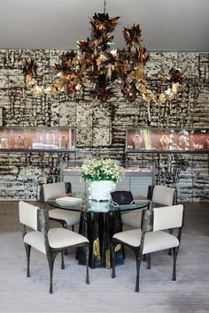 Wall Treatment - A large-scale relief wall design by Peter Lane behind a scuptural chandelier and dining area