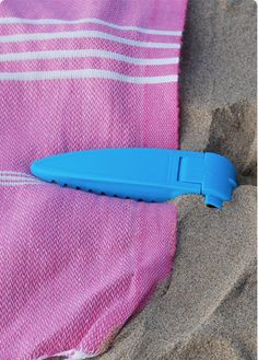 """The Beach Towel Clip anchors your beach towel down in four corners, so it stays where you want it to be, and stays flat when you stretch out in the sun."" I NEED this!"