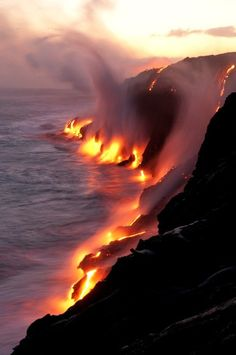 [Lava flowing down from the beach and connecting with the water. By Jennifer Vahlbruch.]