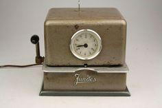 Jundes - elektronische prikklok / stempelklok  Mooie Industriele prikklok/stempelklok gemaakt bij Junde in Duitsland rond 1965. De werknemer stak een prikkaart onder in de klok waarop dan de stempel met de datum en tijd op de kaart kwam te staan. Zo wist de baas precies hoe lang zijn werknemer gewerkt had. Deze Prikklok is in gebruikte conditie de inkt rol is uitgedroogd en er mist een wijzer ook is het slotje defect. Specificaties Merk: JundesModel: 6664 Gewicht: 715 kg Afmeting: 21 x 27 x…