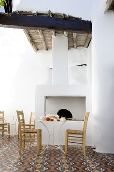 outdoor eating area, mosaic tiles, outdoor fireplace, white walls