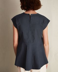 COTTON POPLIN SWING BACK TOP | Crisp cotton poplin with grown-on cap shoulder, round neck with hidden rouleau loop and button fastening at back. Centre seam at front, centre seam to waist at back and flared panel below