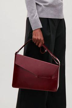 Ich liebe  asymmetrische Linien. Unperfektion kann so perfekt sein!    COS image 7 of Asymmetric leather shoulder bag  in Burgundy
