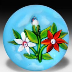 Ronald Hansen two flowers and bud bouquet on blue ground paperweight.
