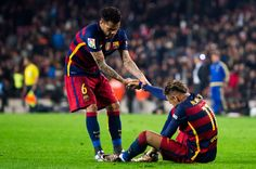 Neymar Santos Jr (R) of FC Barcelona is helped by his teammate Dani Alves as he lays injured after scoring his team's third goal during the Copa del Rey Quarter Final Second Leg between FC Barcelona and Athletic Club at Camp Nou stadium on January 27, 2016 in Barcelona