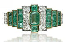 Art Deco 1930s emerald and diamond bracelet of tiered design, centering upon a rectangular-cut emerald flanked on either side with pavé-set diamond bombé panels, to the three rectangular-cut emerald lines and pavé-set diamond bar link bracelet. French assay marks for platinum and gold.