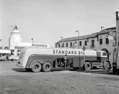 """June 1942. """"Tracy, California. Tank truck delivering gasoline to a filling station."""" Photo by Russell Lee for the Office of War Information.  Flying A."""