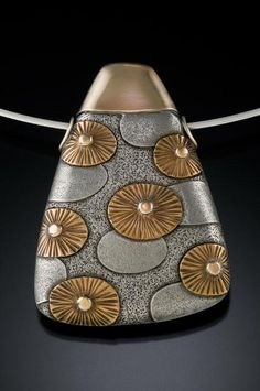 "Pam Caidin, ""The synergy that comes from the juxtaposition of contrasting shape, color and texture intrigues me. The forms are quiet to allow pattern and color to have weight. My intent is to create sculptural jewelry that is elegant and unpretentious.     With the use of a rolling mill, textured fine silver is inlayed with successive layers of rose, yellow & green 14K gold, nickel silver, then handformed into hollow pillows. Patterned pillows are combined with pillows of a single color…"