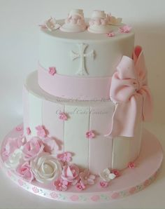 Pretty pink and white striped christening cake, with booties and bow and flowers